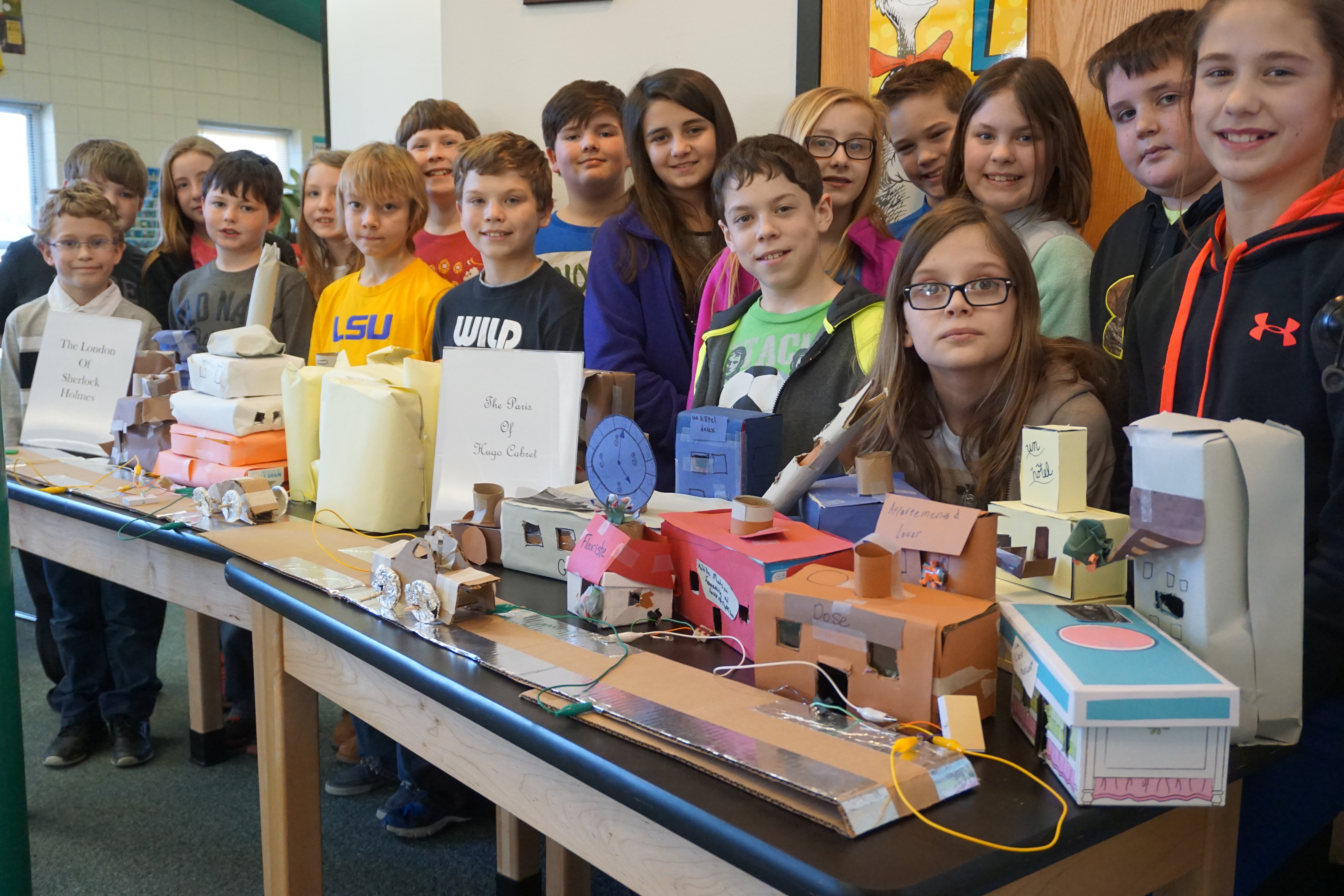 Students pose next to coding projects