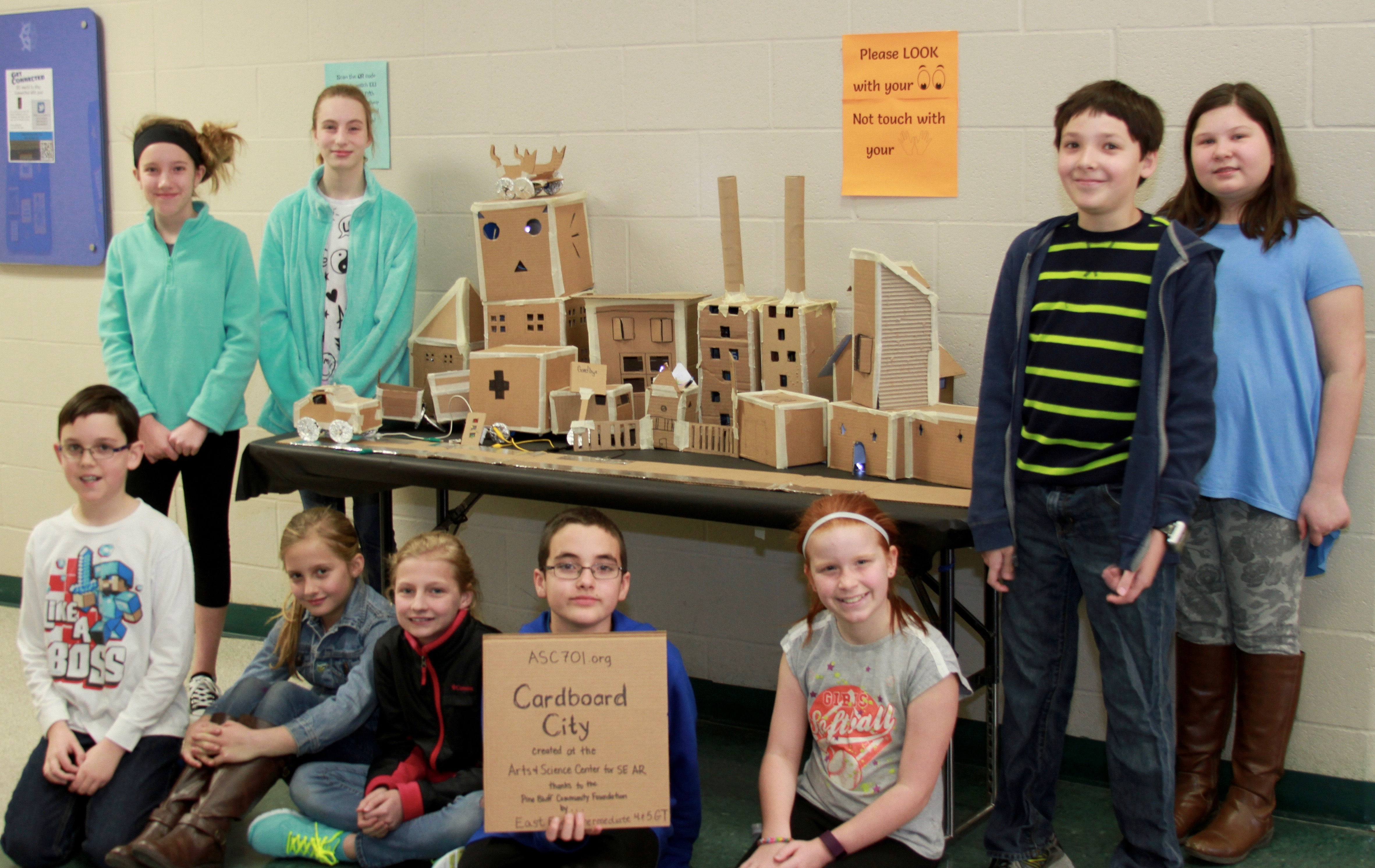 Students pose next to cardboard city
