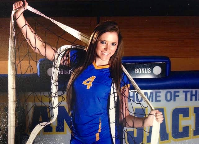 Senior Volleyball Player Sydney Barnett poses with volleyball net