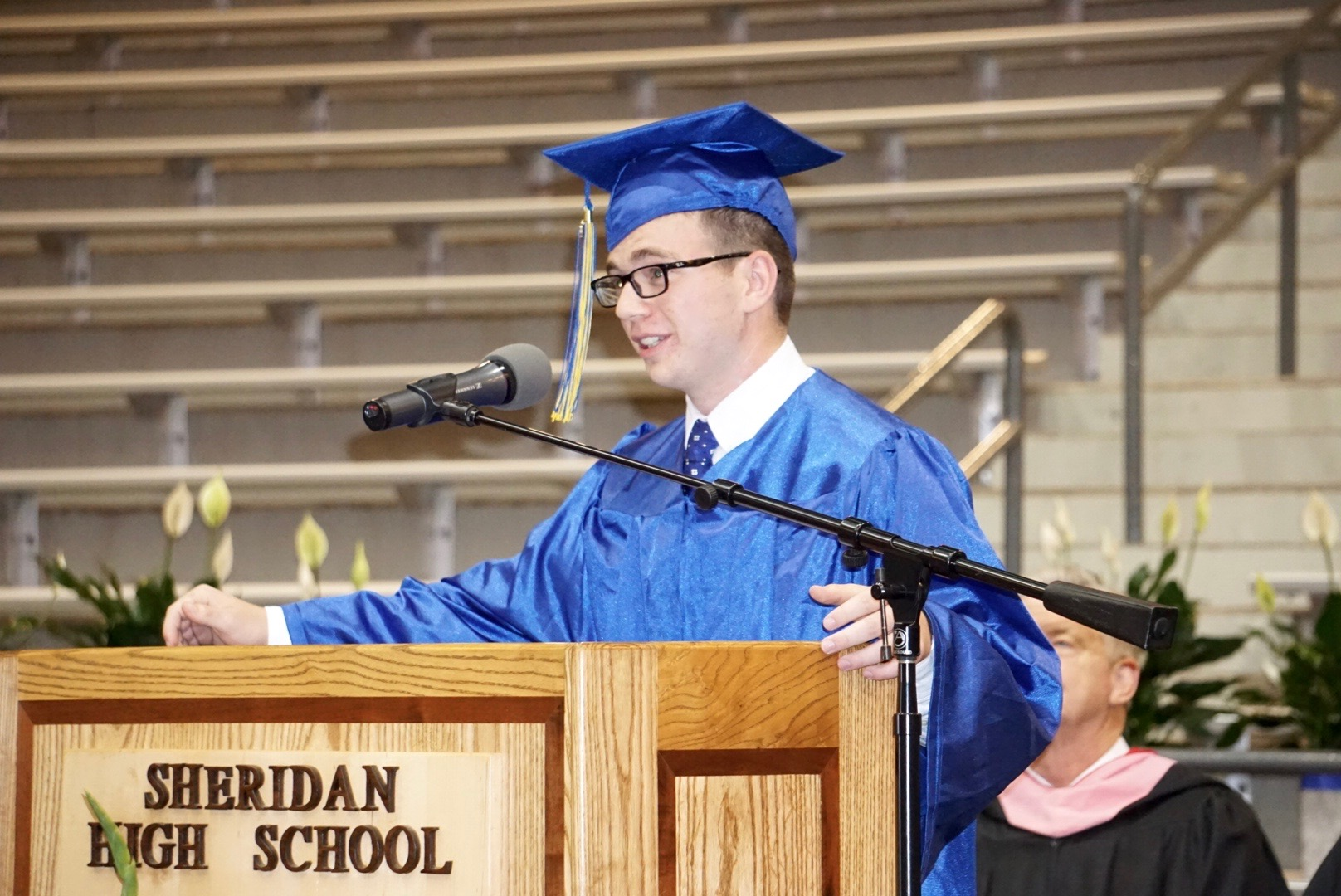 Dylan Thompson giving speech at the podium at graduation