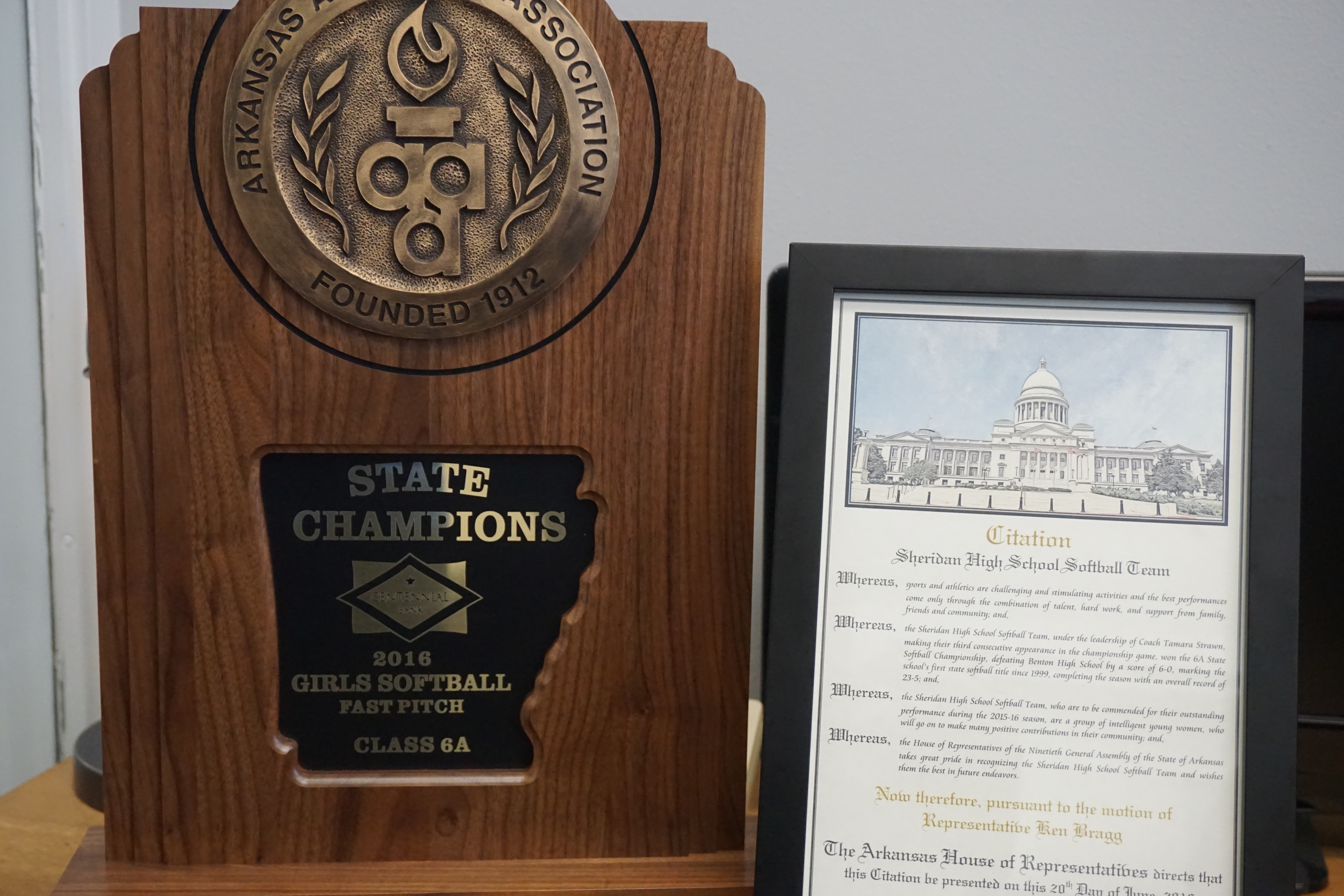 State Champions plaque next to print out of Rep. Ken Bragg's citation
