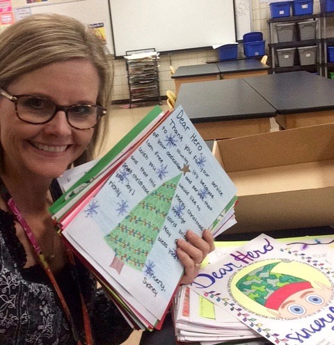 Art teacher poses with the holiday cards her students made for deployed military